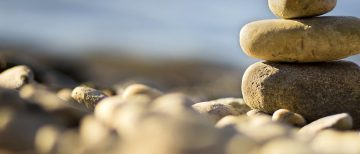 Meditation stones - relaxing on the beach - website banner
